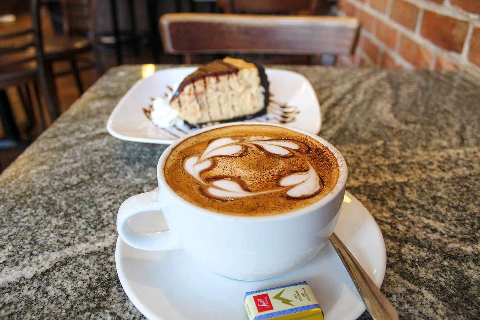 Photo of hearts latte art with a slice of dessert in background