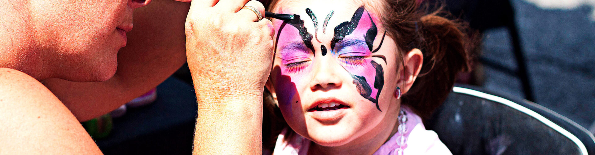 Close-up of a child getting her face painted