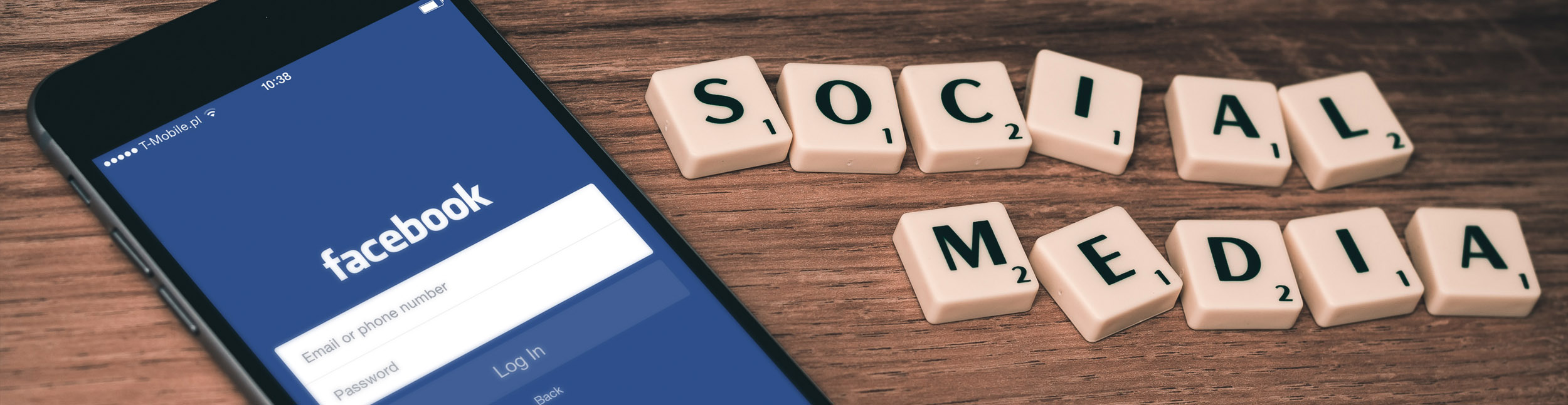iPhone with Facebook log-in display near Social Media scrabble tiles