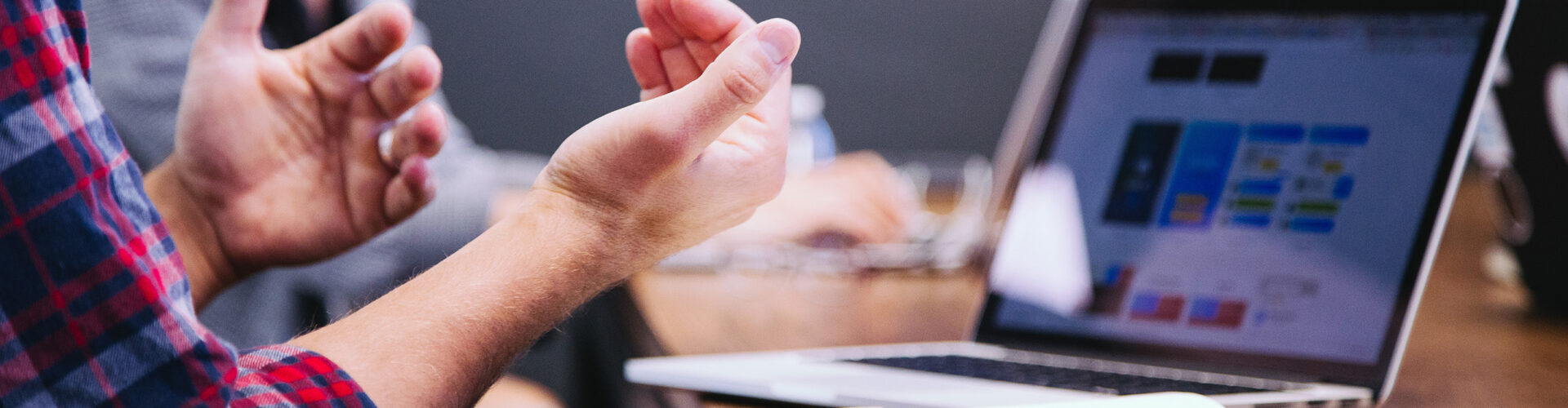 Close-up of person at a board table, gesturing with their hands