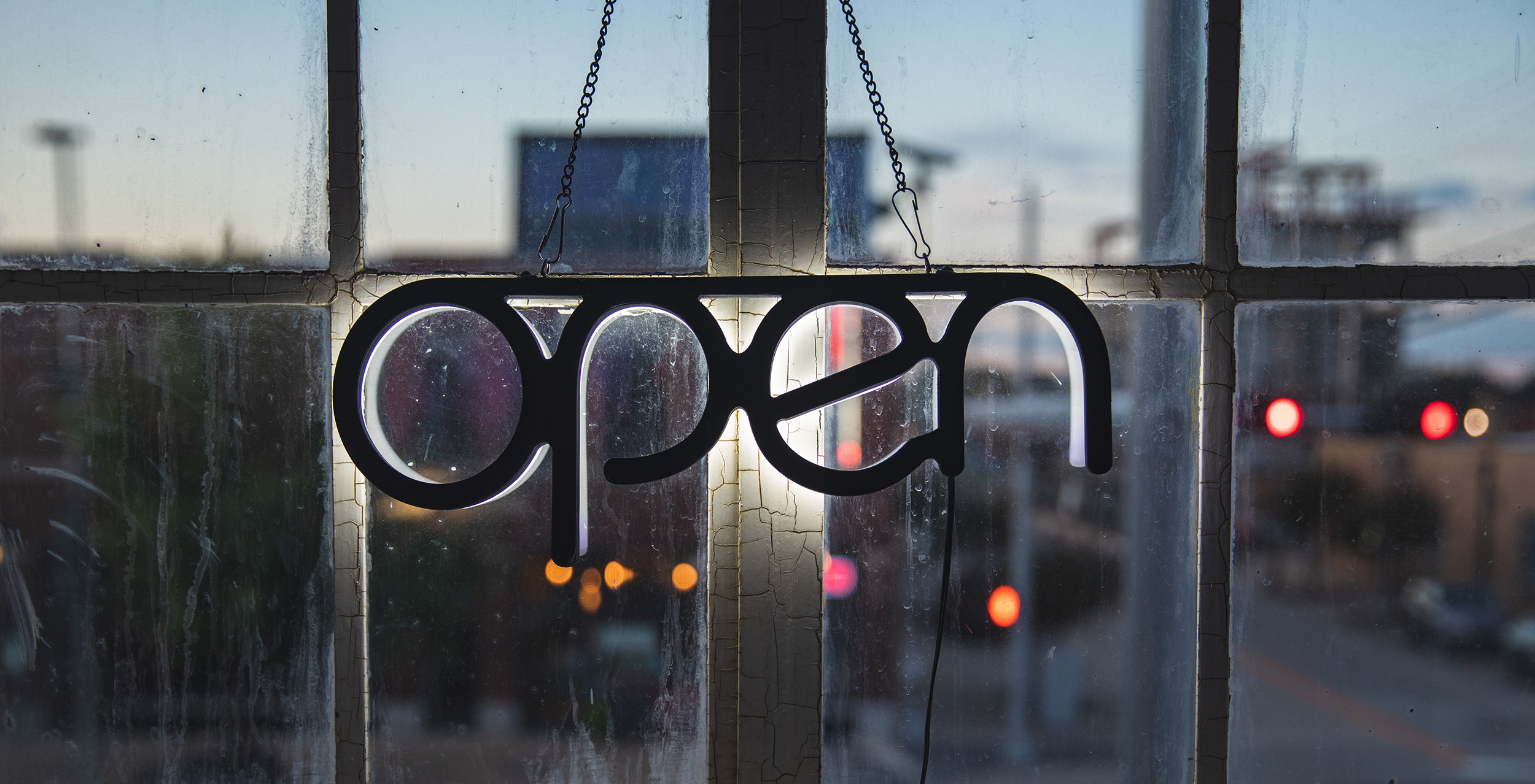 Open sign with backlit lettering hanging in window