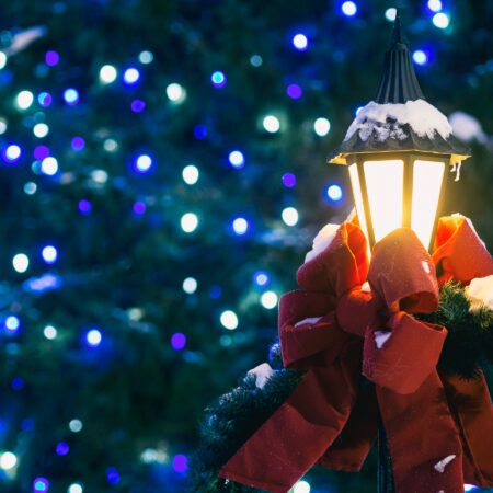 Street lamp with red bow in front of blue and green Christmas lights