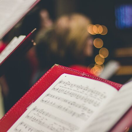 Close up view of sheet music with Christmas lights in the background