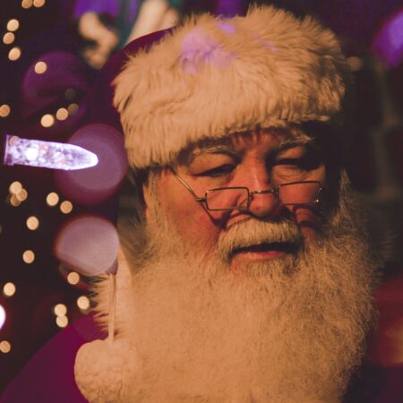 Santa Claus with Christmas lights in the background