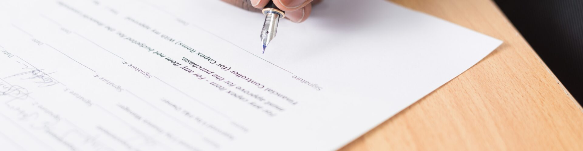 Close up of a person signing a document